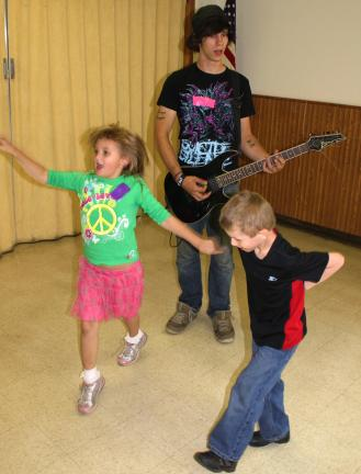 ANDREW LEIBENGUTH/TIMES NEWS Gianna Vought, 6, and Adam Bachert, 6, dance while Cris Dietrich, 21, plays the guitar.
