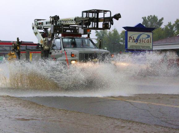A Verizon bucket truck splashes high water as it drives north on Route 309 through flooded roads.