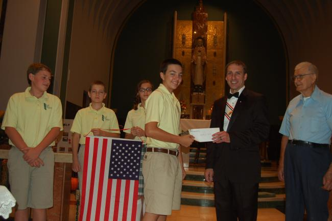 TERRY AHNER/TIMES NEWS  Students at St. John Neumann Regional School's Palmerton campus present a check to Sacred Heart Knights of Columbus of Palmerton members Edward Girard (accepting the check) and Al Kohler during a Mass at the Sacred Heart…