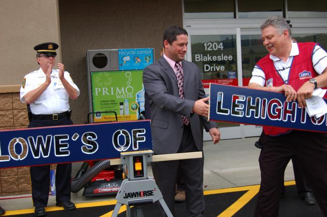 "gail maholick/times news Jonathan J. Cleaver, center, cut the board ""Lowe's of Lehighton"" to officially open Lowe's, Lehighton, at 1204 Blakeslee Boulevard Drive East, Lehighton. On right is store manager, Kerry Collins. Left is Kenneth J. Barnes,…"