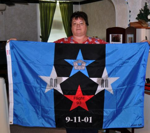 Susan Stine, Tamaqua, displays a Flight 93 memorial flag inside her Dutch Hill house. Stine, a certified nurse's aide, has traveled to the Shanksville crash site on 9-11 for the past ten years.
