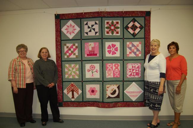 Gail Maholick/TIMES NEWS A scrap of pink polka-dotted fabric was the start of this quilt to promote breast cancer awareness. From left are, Jane Heckman and Cindy Mengel-Smith, co-owners of the Quilted Crow, and Brenda Green and Linda Benner,…
