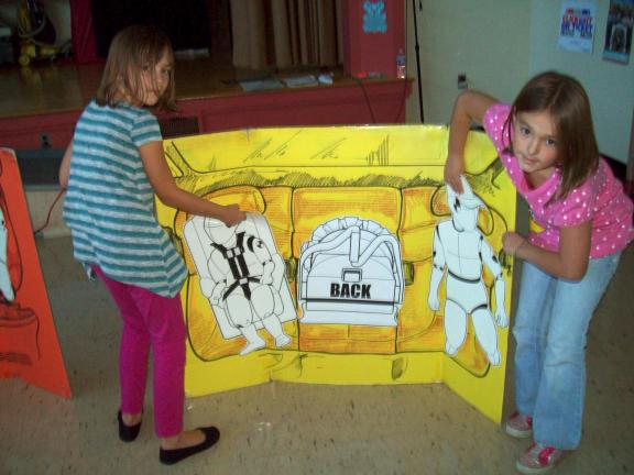 Gail Maholick/TIMES NEWS Mazzy Mickey, left, and Mackenzie Light, demonstrate where children should sit inside a car. They are third-grade students at Mahoning Elementary School.