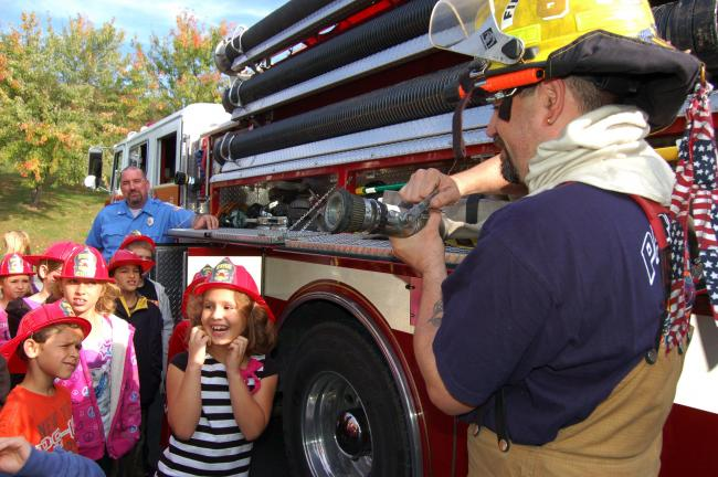 Tom Kobal, firefighter, explains the equipment found inside a firetruck to children at Franklin Elementary School during a Fire Prevention Program at the school.