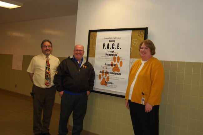 CHRIS PARKER/TIMES NEWS Panther Valley Elementary School Principal William Lombardo, high school Principal Joseph Gunnels and middle school Principal Lisa Mace stand by a poster in the high school promoting positive values.