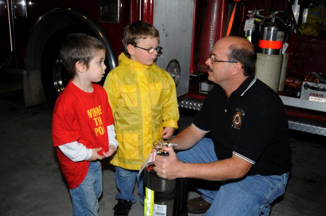 RON GOWER/TIMES NEWS Students from Winnie-the-Pooh pre-school in Summit Hill visited the Diligence Fire Company in Summit Hill during Fire Prevention Week. Shawn Hoben, fire chief, explains fire extinguishers to Levi Weaver, left, and Justin Babinetz.