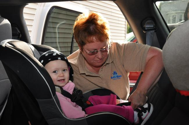 AMY MILLER/TIMES NEWS Evalynn Kuehner, a certified passenger safety technician and member of Safe Kids Carbon County, inspects 14-month-old Lléna DeGennaro's car seat during Tuesday's Head Start car seat checkup in Coaldale. A second car seat…