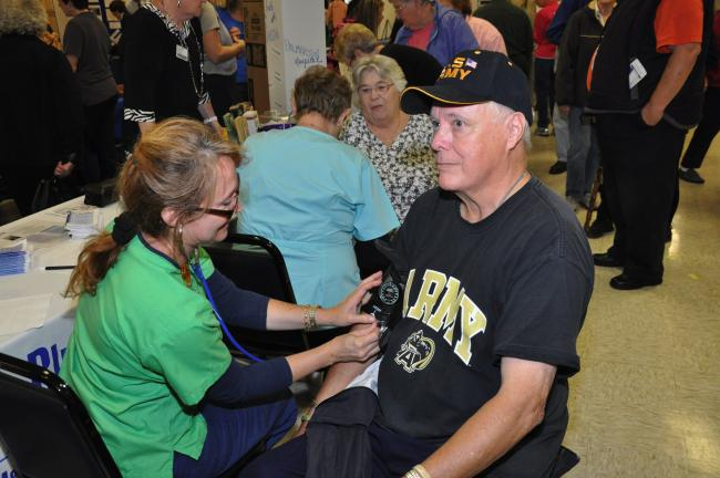 AMY MILLER/TIMES NEWS Vince Gallagher of Lansford, right, takes part in the free blood pressure check at Blue Mountain Health System's table during the Senior Citizens Expo 2011, hosted by state Sens. David G. Argall and John T. Yudichak, and Rep…