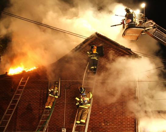 ANDREW LEIBENGUTH/TIMES NEWS Firefighters deal with heavy smoke, congested rooms and exploding ammunition as they battle a house fire that started late Saturday night in New Philadelphia.