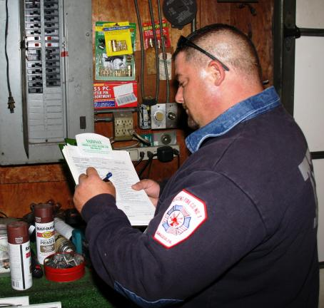 Tamaqua firefighter Travis Heugel inspects a circuit breaker at a local business.