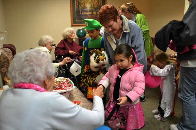 SHERI RYAN/SPECIAL TO THE TIMES NEWS Emma Valderama, 4, of Coaldale receives some candy from Maple Shade Meadows resident Sara Hofford during Safe Trick or Treating on Thursday.