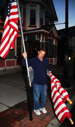 ANDREW LEIBENGUTH/TIMES NEWS Danny Sugden, Tamaqua American Legion member, places a flag in preparation for tomorrow's event.