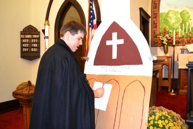 SHERI RYAN/SPECIAL TO THE TIMES NEWS Brian Buzik portrays Martin Luther hammering his Ninety-five Theses to the Castle Church door during a re-enactment at a special Reformation service held at the Zion Lutheran Church, Nesquehoning.