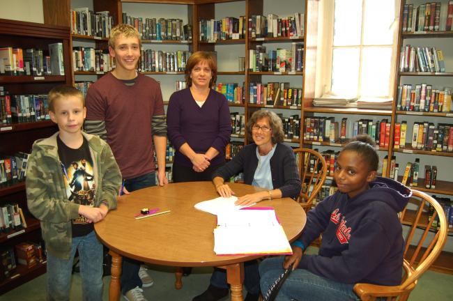 LINDA KOEHLER/TIMES NEWS Left, Kyle Kelshaw, a fifth grader, is getting help in reading from Lisa Koller, a Palmerton Area Junior High School 7th and 8th grade Learning Support teacher and a Homework Helper (second from right) and Dziayah Brown, an…