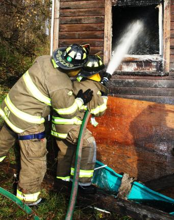 ANDREW LEIBENGUTH/TIMES NEWS Mahanoy City firefighters Todd Dunlap and Ed Peel spray foam on hot spots inside the home.