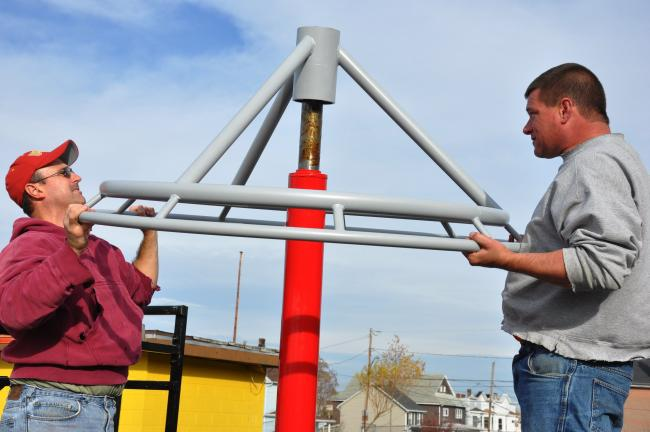 RON GOWER/TIMES NEWS Dan Polak, left, and Mike Kokinda, both of Summit Hill, put the finishing touches on a new maypole at the Ginder Park playground in Summit Hill. It's one of four new rides set for the park.