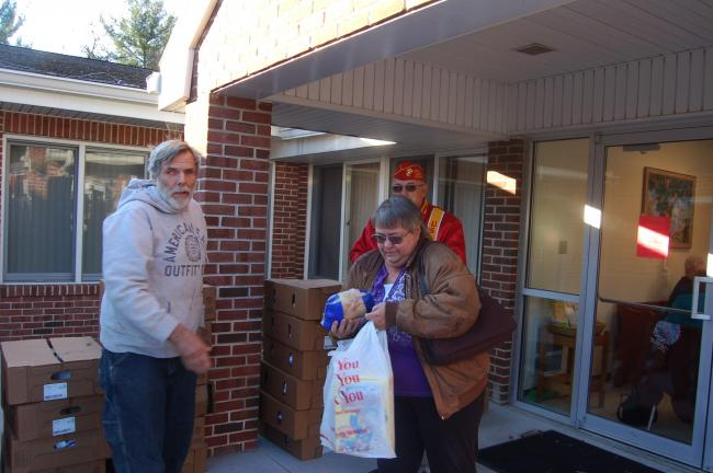 TERRY AHNER/TIMES NEWS Sandra Williamson of Palmerton stuffs her turkey into a bag as volunteer Ed Weiss and Palmerton Lions President George Unangst watch outside St. John's Lutheran Church in Palmerton on Friday.