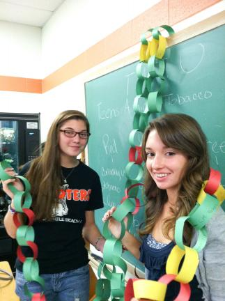 "SPECIAL TO THE TIMES NEWS Weatherly students Dominique Adamczyk, left; and Rachel Moon, show off the paper chain the students made for the ""Great American Smoke-Out."" The colors of the chain are green for non-smokers, yellow for a smoker who has…"
