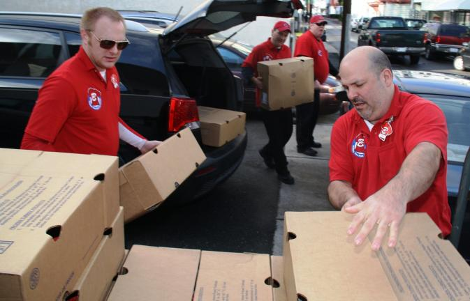 ANDREW LEIBENGUTH/TIMES NEWS Helping Salvation Army volunteers unload turkeys prior to the food distribution are Justin Hunsicker, assistant manager, left, and store manager Mike Casella, of the Tamaqua Boyer's Food Market.