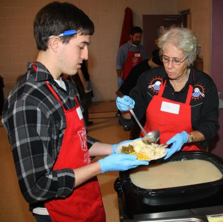 ANDREW LEIBENGUTH/TIMES NEWS Salvation Army volunteers Fran Stahl, Tamaqua, right, and Anthony Bear, 18, Lehighton, pour gravy on a visitors Thanksgiving platter.