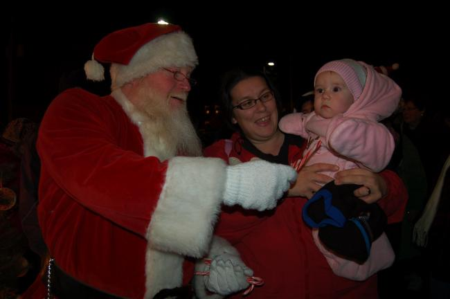 Gail Maholick/TIMES NEWS With a look of amazement, Addison Ahner, 6-month old daughter of Lisa and Dale Ahner, accepts her first candy cane from Santa.