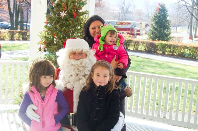 TERRY AHNER/TIMES NEWS  Santa Claus greets Grace Sterling, 5, Caroline Sterling, 6, mother Jillyan Sterling and Ava Sterling, 1, in the Palmerton Borough Park bandstand as part of his visit on Saturday.