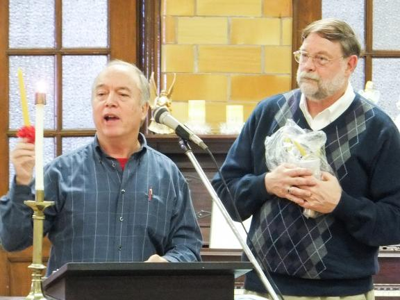 CONTRIBUTED PHOTO BY JAMES STOVES Tim Gilman of the Bethlehem (Pa.) Christmas City Citizens Committee, explains the symbolism associated with the Moravian beeswax candle. Gilman presented the beeswax candles to George Taylor of the Tamaqua Area…