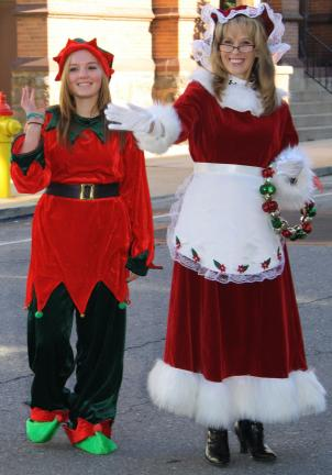 ANDREW LEIBENGUTH/TIMES NEWS Morgan Rosohac, 16, playing Santa's elf, walks with Mrs. Claus, played by Renee Slakoper, outside the Lansford Mini Mall on West Ridge Street.