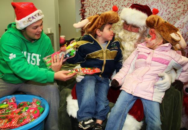 ANDREW LEIBENGUTH/TIMES NEWS Wearing Rudolph hats while sitting on Santa's lap are Hayden Magrini, 3, and Kristen Brinich, 5. Also pictured is elf and key volunteer Michelle Mehallic.