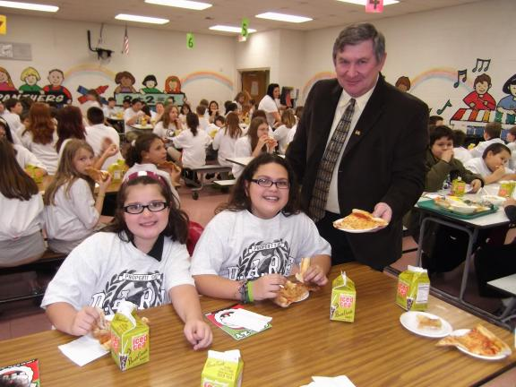 CAROL ZICKLER/SPECIAL TO THE TIMES NEWS Nesquehoning Mayor Tony Walck serves pizza to two fifth grade DARE students at Panther Valley Elementary School. Seen are Emily Evans, left, and Sophia Tuccillo enjoying their pizza and ice tea.