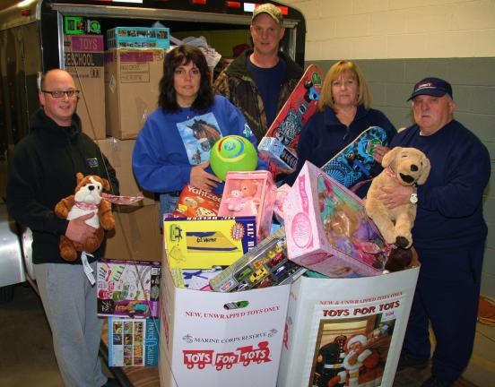ANDREW LEIBENGUTH/TIMES NEWS Pictured in front of a trailer of toys are, from left, Rush Township Police Officer Duane Frederick, Rush Twp supervisors Jeanine Motroni, Shawn Gilbert, volunteer Cindy Messerschmidt and fire police volunteer Merle Wertman.