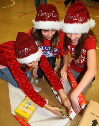 ANDREW LEIBENGUTH/TIMES NEWS 5th graders Morgan Lusch, 10, left, Angeline Castagna, 11, center, and Emily Amershek, 10, wear holiday caps as they race against other groups to be the first to wrap a gift box.