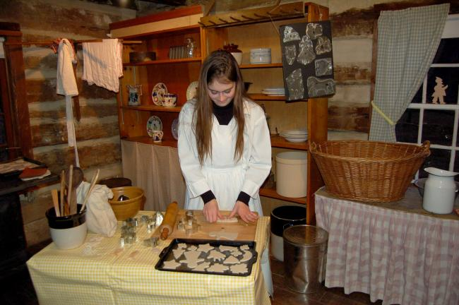 "LINDA KOEHLER/TIMES NEWS As a ""daughter"" of the house, Samantha Krabutler demonstrates what it was like making cookies in the 1890s. ""Mama says if you don't fill a wash basket full, you didn't bake enough."" She explained that almost all the…"