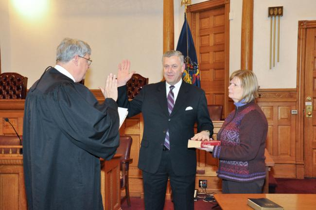 AMY MILLER/TIMES NEWS William J. O'Gurek, center, is sworn into office as Carbon County's minority commissioner by President Judge Roger N. Nanovic II, left, during an impromptu swearing-in ceremony Tuesday afternoon. Holding the Bible for O'Gurek…