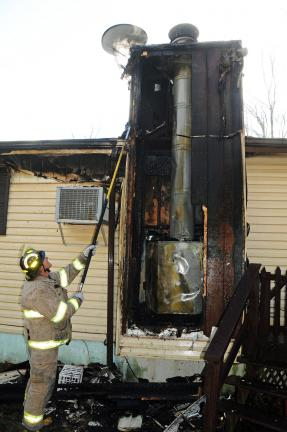 A fireman probes the damaged heating unit, source of Wednesday's fire.
