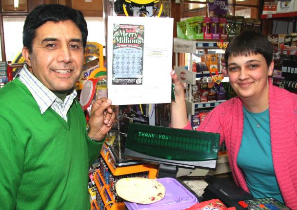 ANDREW LEIBENGUTH/TIMES NEWS Shahid Chaudhry, owner of The Brown Bag grocery store in Barnesville, and Amanda Titus, manager, hold an enlarged copy of the million dollar scratch-off ticket that was sold Monday.