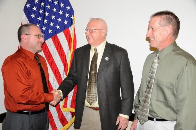 RON GOWER/TIMES NEWS Neal Ebbert, left, is congratulated on his appointment as new chief of police in Lehighton by Grant Hunsicker, center, president of Lehighton Borough Council. Looking on is Mayor Donald Rehrig.