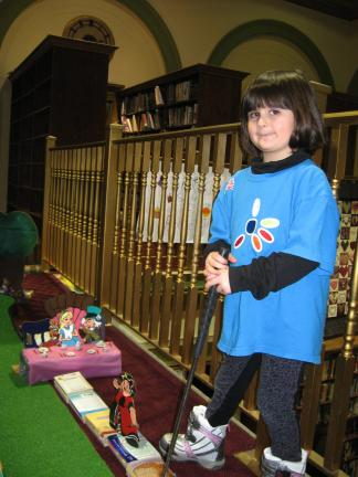 "001 Daisy Girl Scout Nicollette McCabe lines up a putt on the ""Alice in Wonderland"" green during miniature golf at Library Palooza at the Palmerton Area Library."