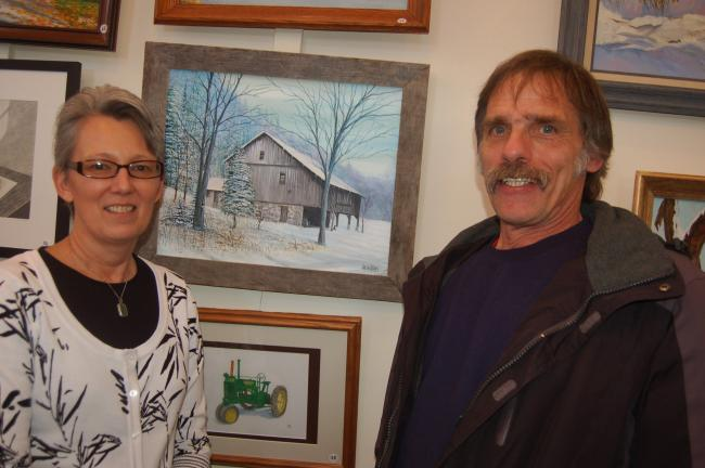 TERRY AHNER/TIMES NEWS Diane Danielson, director, Palmerton Area Library, and artist Douglass Wilkins, of Neola, showcase a painting of an old mill in Sciota (center) that Wilkins submitted for the library's sixth annual Art Show on Sunday. The…