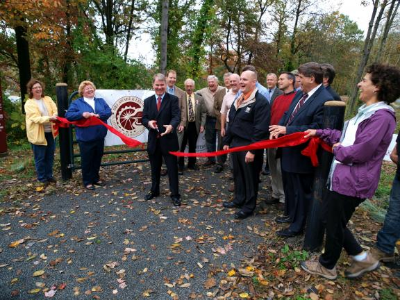 Elissa Garofalo (far right) holds ribbon as it is cut by State Senator Dave Argall to celebrate the opening of a 2.9 mile section of the Delaware & Lehigh Trail between East Penn Township and the Lehigh Gap last October.