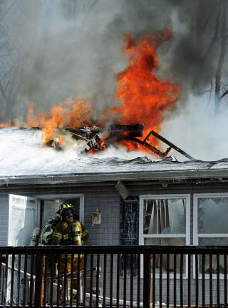 Flames rip through the roof of a home at 4780 Forest St., Towamensing Township on Tuesday afternoon. Living in the home were Bob Proulx, 79, and his son, John.