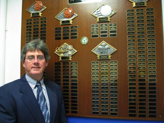 Bill O'Gurek/times news Youth basketball coach Gene Binder proudly shows some of his teams' accomplishments at St. Joseph Regional Academy in Jim Thorpe.