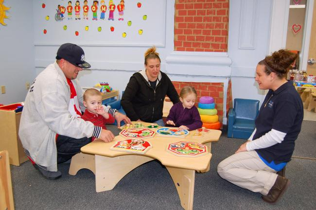 CHRIS PARKER/TIMES NEWS Robert Perez, holding son Brayden, Theresa Perez, with daughter Jaylyn, and Early Head Start home visitor Cerissa Kibler, play with puzzles in the Coaldale center.