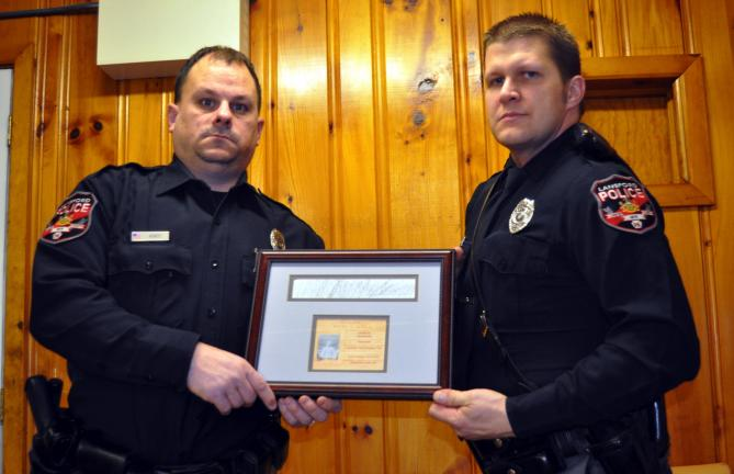 DONALD R. SERFASS/TIMES NEWS Lansford Police Officer Brian Horos, left, and Officer Chris Ondrus, display the pencil etching of fallen Officer Morgan Morgans' engraved name as seen on the Fallen Officers Memorial, Washington, D. C.