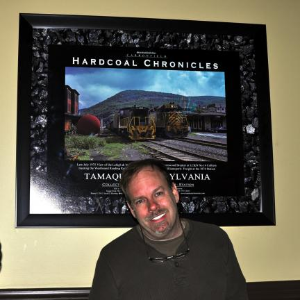 DONALD R. SERFASS/TIMES NEWS Tamaqua native Scott D. Herring of Red Oak, Texas, stands in front of an image he presented this week to Tamaqua SOS as part of the launch of the Hardcoal Chronicles 40th Anniversary, a compilation of almost 150,000…