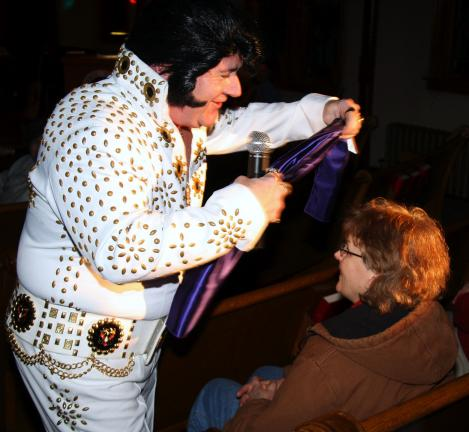 ANDREW LEIBENGUTH/TIMES NEWS Elvis Presley tribute artist Johnny M wraps a purple scarf around Marlene Basiago, Summit Hill.