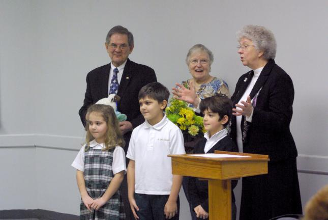 Special to the TIMES NEWS Kindergarten pupils at St. John Neumann Regional School's Slatington campus recently presented Joseph and Isa Bechtel of Slatington with flowers and a stuffed sheep as Principal Sister Virginia Stephanie watches on, as part…