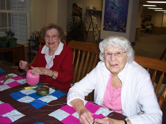 Special to the TIMES NEWS Village at Palmerton residents Naomi Smith and Erma Gregory knot a handmade quilt.