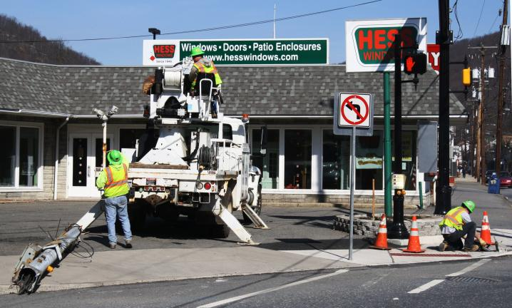 ANDREW LEIBENGUTH/TIMES NEWS Workers with Bruce & Merrilees Electric Company, a PennDOT contractor, take down the remnants of the old traffic light at the intersection of Mauch Chunk and Pine Street (SR309) in Tamaqua.