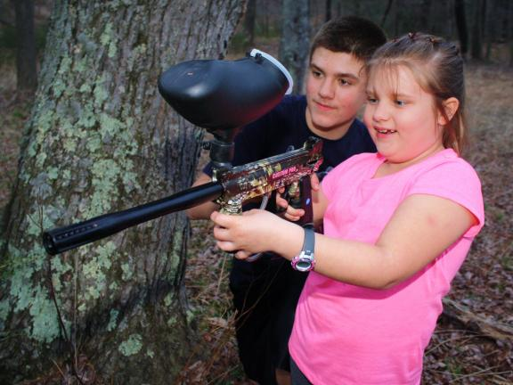 ANDREW LEIBENGUTH/TIMES NEWS 70 degree weather over the past few days made for fun times for families throughout our area. In the woods near Middleport, Dylan Stillwagner, 12, shows his cousin Kerra Dempsey, 7, how to use a paintball gun.